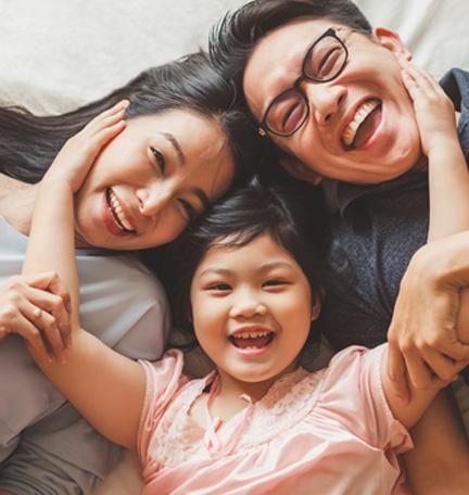 familia feliz en la cama riendo y abrazándose