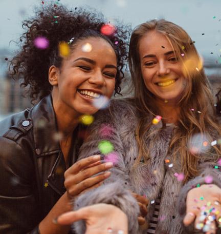 dos muchachas celebrando con papel picado