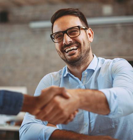 joven profesional masculino sonriéndo y estrechando manos con un colega