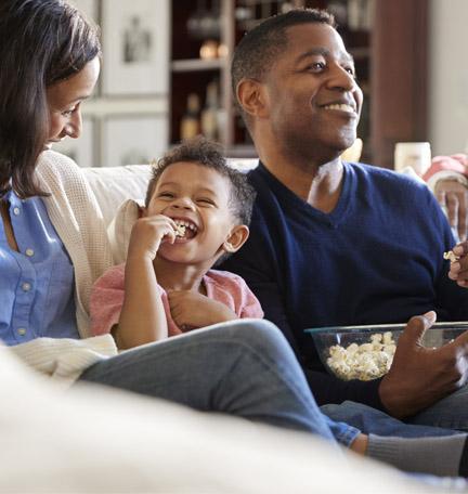 tres generaciones de una familia, felices, mirando una película y comiendo palomitas de maíz