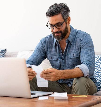 hombre leyendo facturas en su sofá