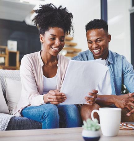 pareja afroamericana sentada en un sofá leyendo documentos