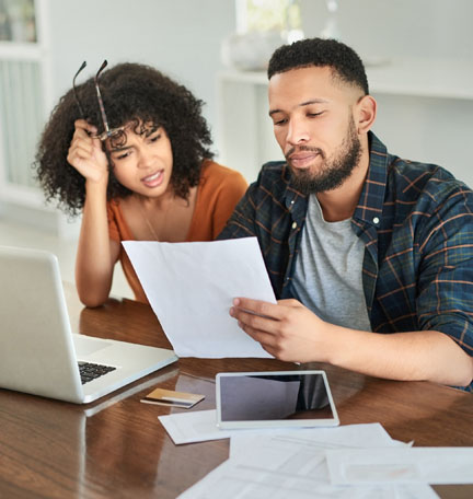Shot of a young couple looking stressed while going over their finances at home