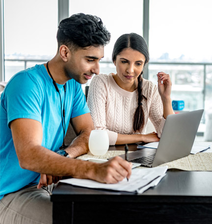 Young Indian couple working on home budget