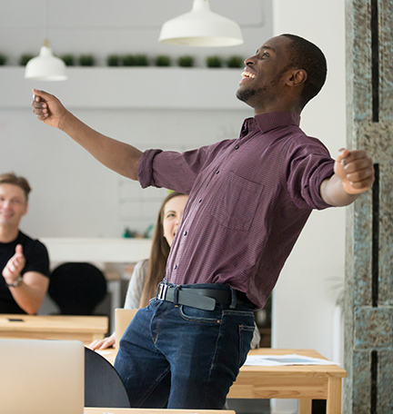 Excited man celebrating success with co-workers.