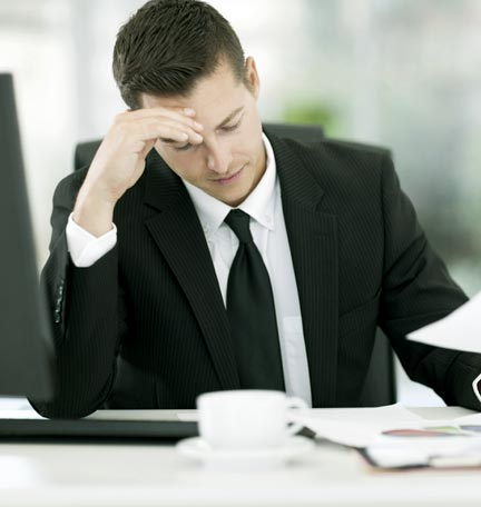 Man sitting at desk looking at time management reports