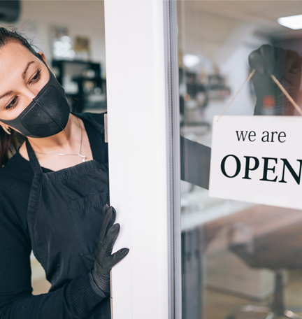 """Comerciante feliz colgando un cartel que dice """"abierto"""" durante la pandemia del COVID-19."""