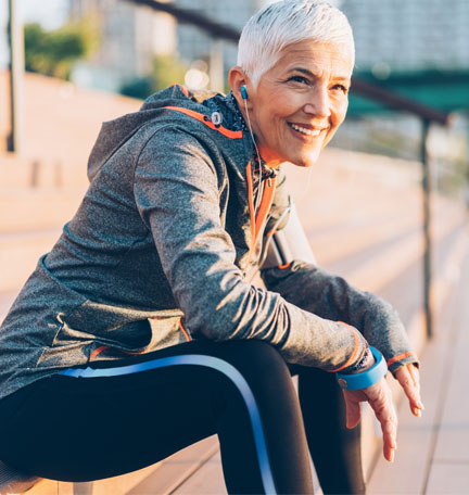 female senior sitting on a bench after a run