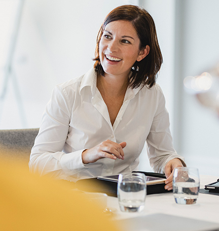 Businesswoman smiling at meeting table, listening, learning, success, happiness