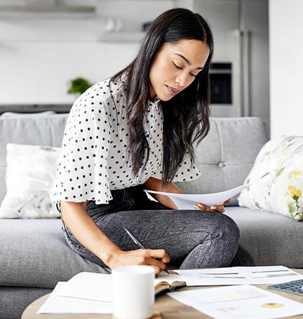 Mujer joven analiza facturas mientras escribe en una agenda. Mujer utiliza una tableta digital en la mesa. Está sentada sobre un sofá en casa.