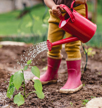niño con botas de lluvia regando plantas