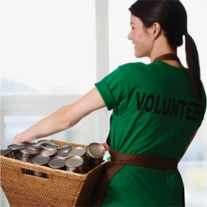 Woman carring basket of can goods wearing a volunteer t-shirt